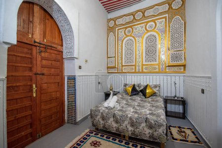 Photo for Fes, Morocco - 11.02.2020: Interior of Moroccan riad. Inner courtyard with tiled walls and floor from mosaic. Traditional ornate and colorful arabesque wall carvings above an archway. - Royalty Free Image