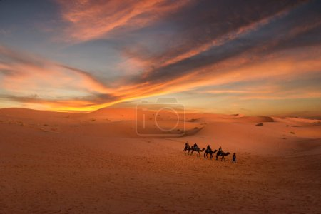 Photo for Amazing sunset over the dunes Erg Chebbi in the Sahara desert near Merzouga, Morocco , Africa. Beautiful sand landscape with stunning sky. Camel caravan of people going through the sand dunes . Maroc - Royalty Free Image