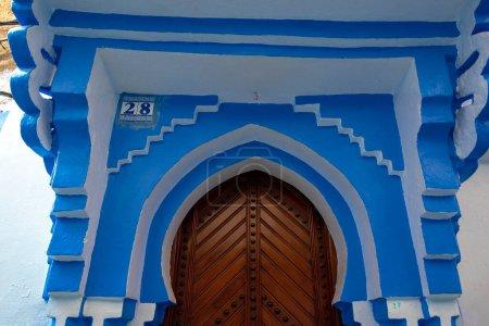 Photo pour Typique, vieux, bleu finement sculpté, clouté, riad marocain porte et porte-cadre et vieille maison. Belle vue sur la ville bleue dans la médina. Maisons peintes à CHEFCHAOUEN, MAROC - image libre de droit