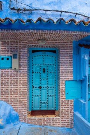 Photo pour Typique, vieux, bleu finement sculpté, clouté, riad marocain porte et cadre de porte et vieille maison à CHEFCHAOUEN, MAROC. Belle vue sur la ville bleue dans la médina. maisons peintes - image libre de droit