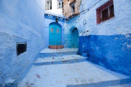 Photo pour Belle vue sur la ville bleue CHEFCHAOUEN, MAROC dans la médina. Détails architecturaux marocains traditionnels et maisons peintes. rue avec porte et murs bleu vif avec arche - image libre de droit