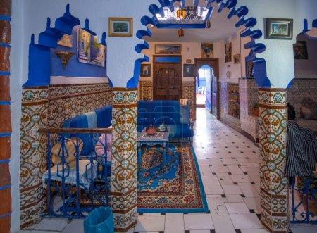 Photo pour CHEFCHAOUEN, MAROC - 12.07.2019 : Cour intérieure avec murs carrelés et sol en mosaïque. Sculptures murales arabes traditionnelles ornées et colorées au-dessus d'une arche dans le riad marocain. Intérieur intérieur - image libre de droit