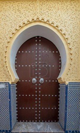 Photo pour Rabat, Maroc. Design traditionnel marocain d'une ancienne porte d'entrée en bois. Dans la vieille Médina. Typique, vieux, brun finement sculpté, clouté, porte riad marocaine - image libre de droit