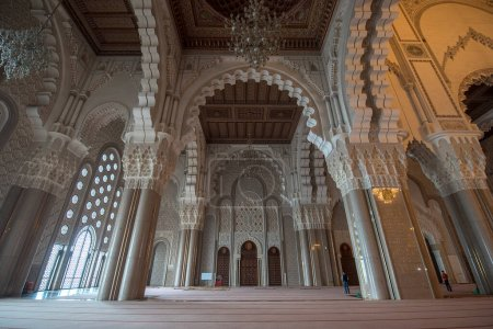 Photo for Casablanca, Morocco - 03.02.2020: Hassan II Mosque interior corridor with columns. Arabic arches, ornaments, chandelier and lighting. It is the largest mosque in Maroc. - Royalty Free Image