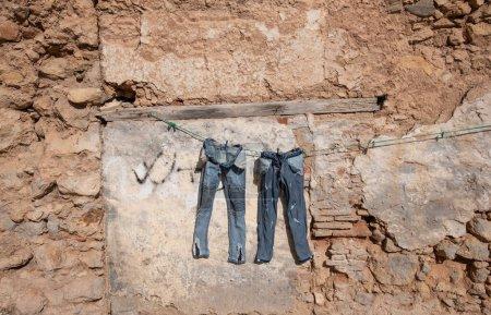 Photo pour Jeans blanchis vêtements laissés à sécher dans la rue dans la vieille ville d'El Jadida, Maroc. - image libre de droit