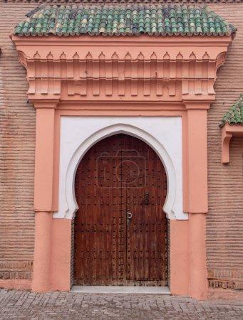 Photo pour Design traditionnel marocain d'une ancienne porte d'entrée en bois. Dans l'ancienne médina de Marrakech, au Maroc. Typique, vieux, brun finement sculpté, clouté, porte riad marocaine - image libre de droit