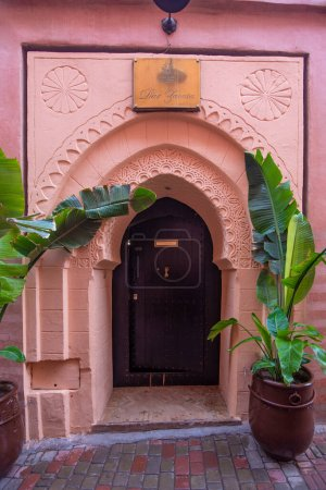 Photo for Traditional Moroccan style design of an ancient wooden entry door. In the old Medina in Marrakech, Morocco. Typical, old, brown intricately carved, studded, Moroccan riad door - Royalty Free Image