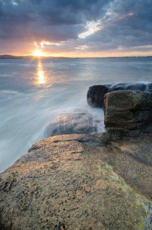 Photo pour Un beau lever de soleil nuageux à la partie pierreuse de la côte sud-est de la mer Noire, prise dans la région de Burgas, Bulgarie. Beau paysage de mer avec des pierres et un ciel ardent - image libre de droit