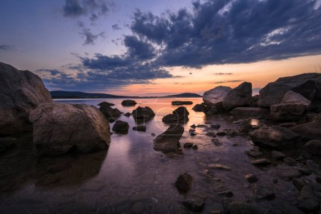 Photo for A beautiful cloudy sunset at the stony part of south-east Black Sea coast, taken in the area of Burgas, Bulgaria. Beautiful sea scenery with stones and fiery sky - Royalty Free Image