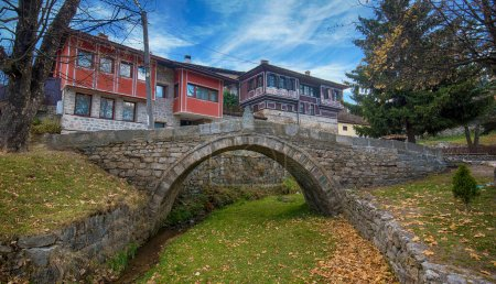 Photo for Old roman stone bridge and old bulgarian traditional houses in Koprivshtitsa, Bulgaria in autumn - Royalty Free Image