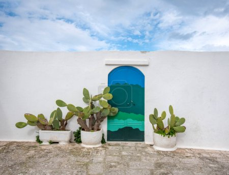 Photo for Blue door with cactus and the traditional white walls in the town of Ostuni Apulia region, Italy - Puglia. With clouds sky. - Royalty Free Image