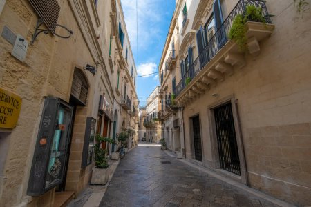 Photo for Lecce, Puglia, Italy - March 08, 2019: Medieval street and historical center in the old town. View and detail of an ancient gate or door, statues and facade of houses. A region of Apulia - Royalty Free Image