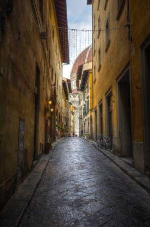Photo for Florence, Italy - 16 February, 2019: a street overlooking The Duomo in Florence, the Cathedral of Santa Maria del Fiore - Royalty Free Image