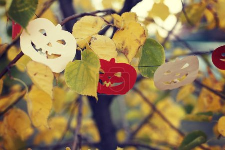 Photo for Closeup of Halloween decorations hanged on branches of autumn colored tree with leaves - Royalty Free Image