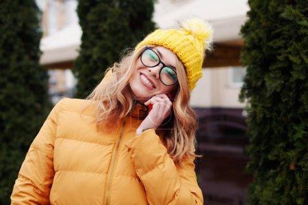 Photo pour Femme en manteau orange en utilisant smartphone dans la rue en hiver - image libre de droit