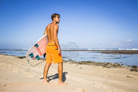 young surfer with surfing board standing on sandy beach on summer day