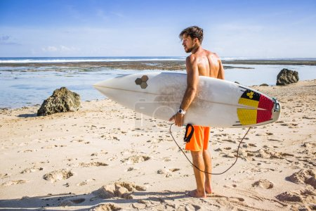 side view of young surfer with surfing board standing on sandy beach on summer day