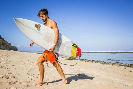 Photo for Young athletic sportsman with surfing board walking on sandy beach - Royalty Free Image