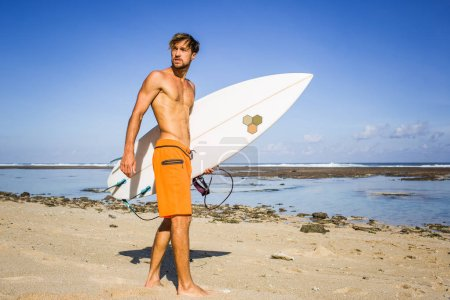 Photo for Young surfer with surfing board standing on sandy beach on summer day - Royalty Free Image