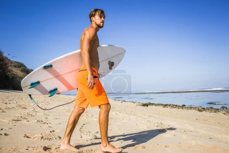 side view of young athletic sportsman with surfing board walking on sandy beach