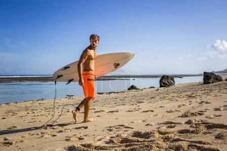 young athletic sportsman with surfing board walking on sandy beach