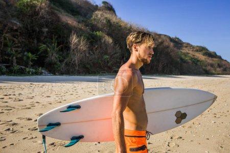 vue latérale de l'homme avec surf Conseil vous cherchez loin sur la plage de sable fin