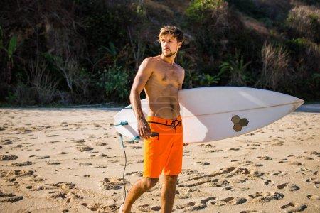 Photo pour Homme sportif avec planche de surf regardant loin sur la plage de sable - image libre de droit