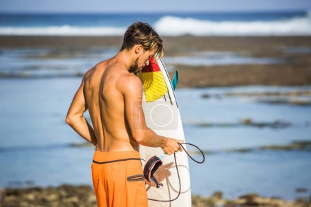 side view of athletic sportsman with surfing board on coastline on summer day