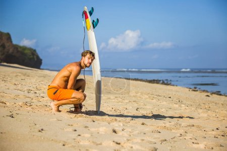young man with surfing board on sandy beach near ocean