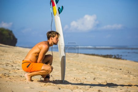 Photo for Side view of young man with surfing board on sandy beach near ocean - Royalty Free Image