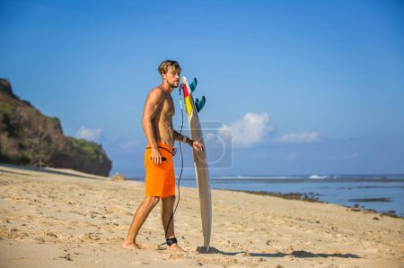 side view of young man with surfing board on sandy beach near ocean