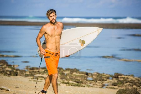 Photo for Surfer with surfing board running on sandy beach on summer day - Royalty Free Image