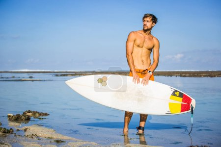 athletic sportsman with surfing board looking away on coastline on summer day