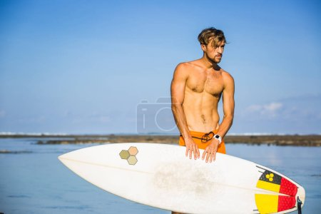 Photo for Athletic sportsman with surfing board on coastline on summer day - Royalty Free Image