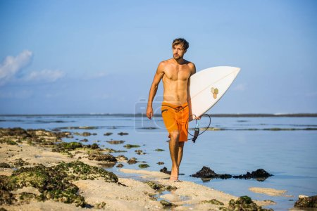young sportsman with surfing board walking on sandy beach