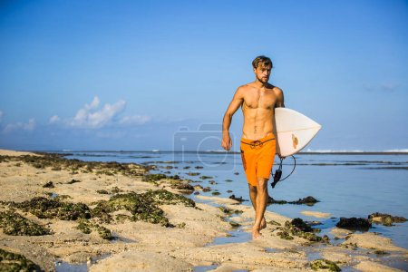 Photo for Young sportsman with surfing board walking on sandy beach - Royalty Free Image