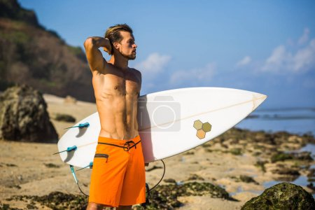 young surfer with surfing board standing on sandy beach near ocean