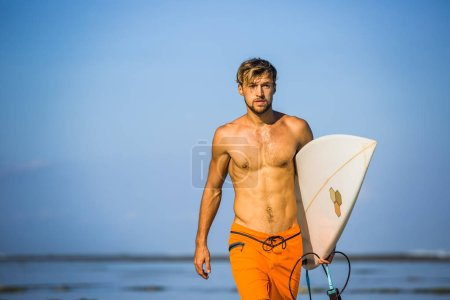 Photo for Portrait of athletic sportsman with surfing board on coastline on summer day - Royalty Free Image