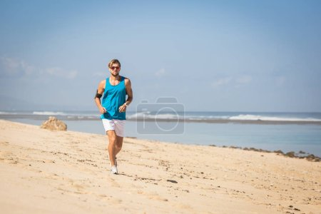 handsome sportsman running on sea shore