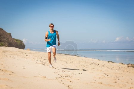 sportsman running on sand beach near sea, Bali, Indonesia