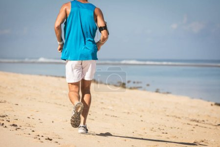 back view of runner training on sand beach near sea, Bali, Indonesia