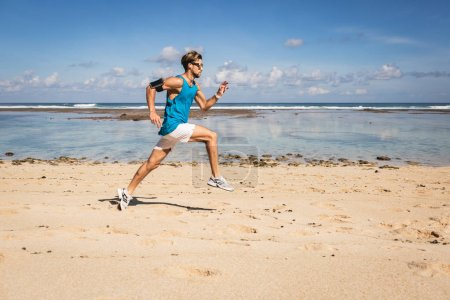Photo for Sportsman jogging and jumping on sand beach near sea, Bali, Indonesia - Royalty Free Image