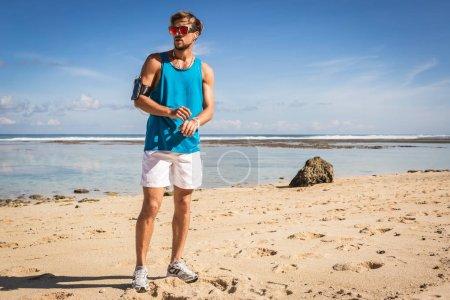 Photo pour Beau sportif en lunettes de soleil avec brassard se tenant debout sur la plage, Bali, Indonésie - image libre de droit