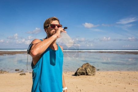Photo for Athletic man with smartphone armband drinking water from sports bottle on seashore - Royalty Free Image