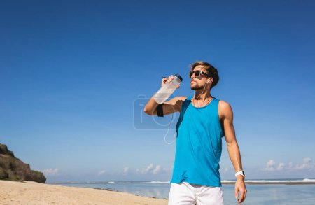 Photo for Sportsman in sunglasses drinking water from sports bottle on beach - Royalty Free Image