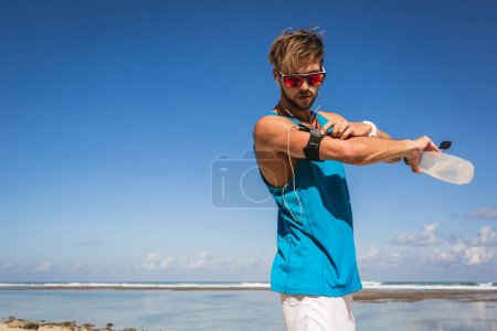 Photo pour Homme athlétique avec bouteille de sport en utilisant smartphone dans le brassard près de la mer - image libre de droit