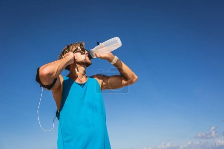 Photo for Athletic man drinking water from sports bottle - Royalty Free Image