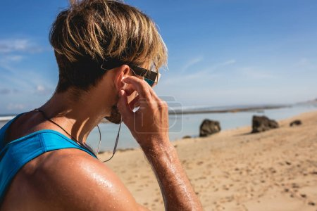 athletic man listening music with earphones on beach