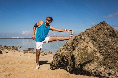 sportive man stretching leg near rock on beach