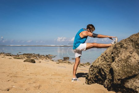 athletic man stretching leg near rock on beach